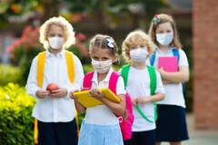 Des enfants portant le masque en route pour l